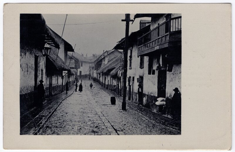 """""""A typical street of this city, showing houses with thatched roofs and the open sewerage system still used here"""""""